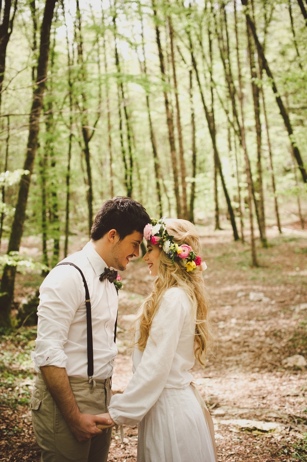 Bride and groom touching heads in woods