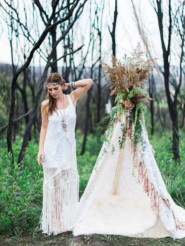 Bohemian bridesmaid standing next to tipi