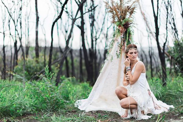 Bohemian bridesmaid crouching next to tipi