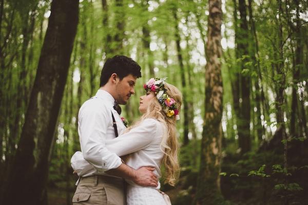 Bride and groom hugging in woods
