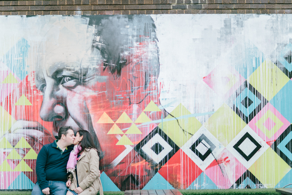 Couple kissing in front of graffiti wall in Shoreditch