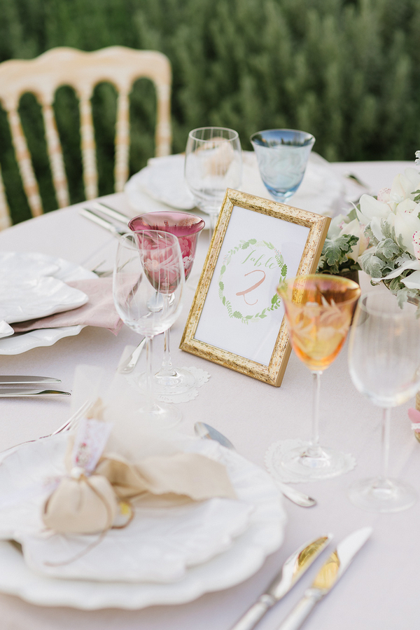 Table number and coloured glasses on wedding table