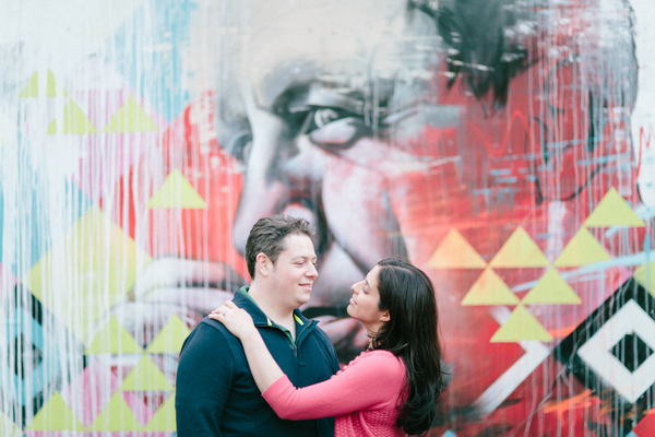 Couple standing in front of graffiti wall in Shoreditch