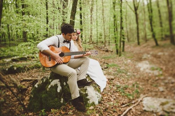 Groom playing guitar to bride in woods