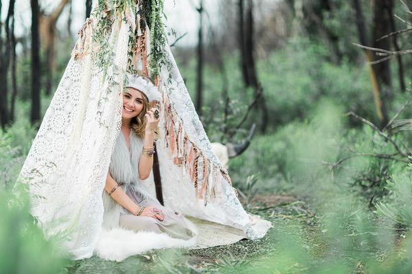 Bohemian bridesmaid sitting in tipi