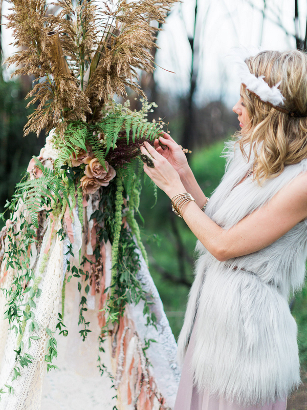 Bohemian bridesmaid touching foliage on tipi