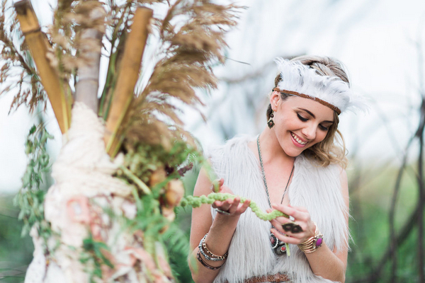Bohemian bridesmaid holding foliage from tipi