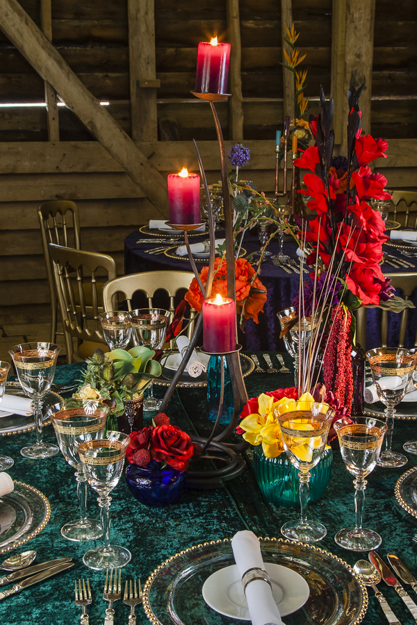 Wedding table with colourful candles, glasses and flowers