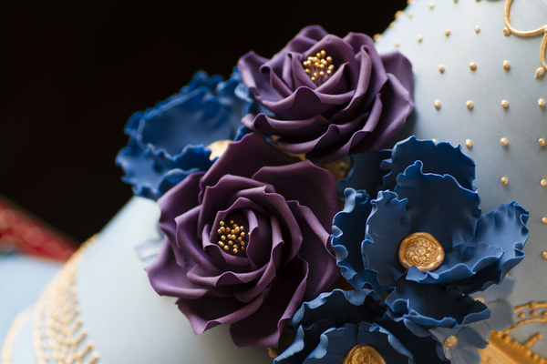Purple and blue sugar flowers on wedding cake