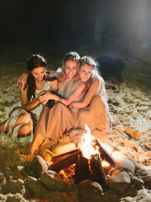 Bohemian bridesmaids sitting by fire on beach