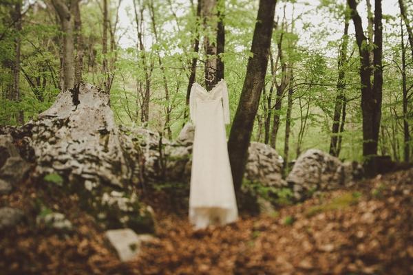Vintage wedding dress hanging in woods