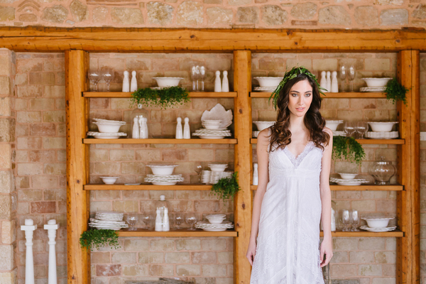 Bride standing in front of shelves of crockery