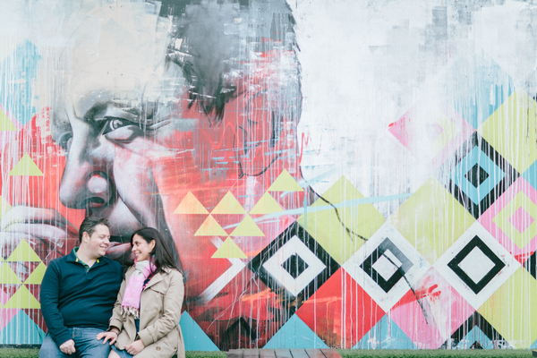 Couple in front of graffiti wall in Shoreditch