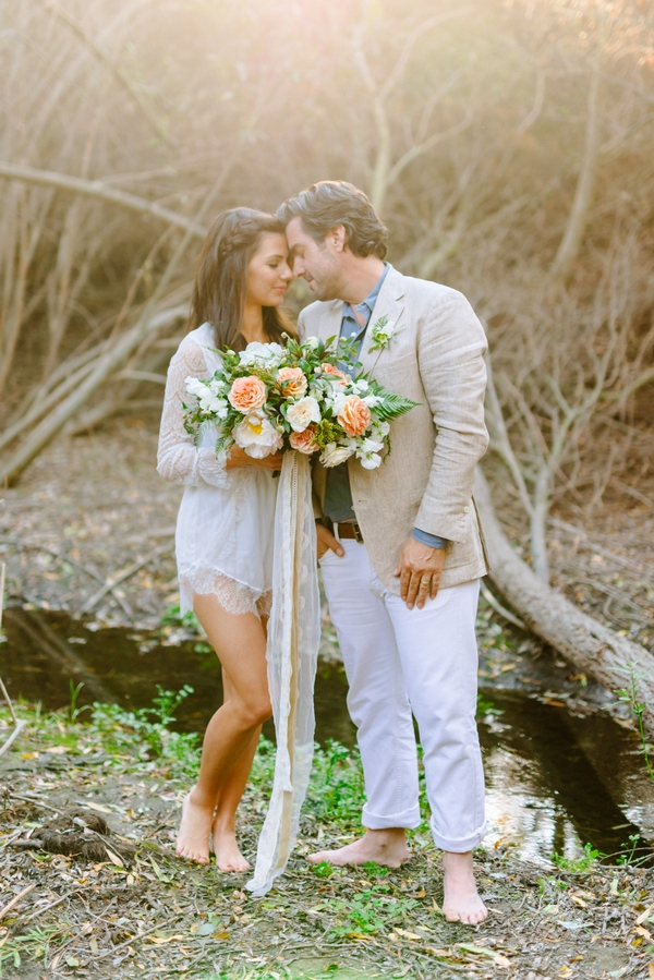 Bride and groom touching heads next to creek
