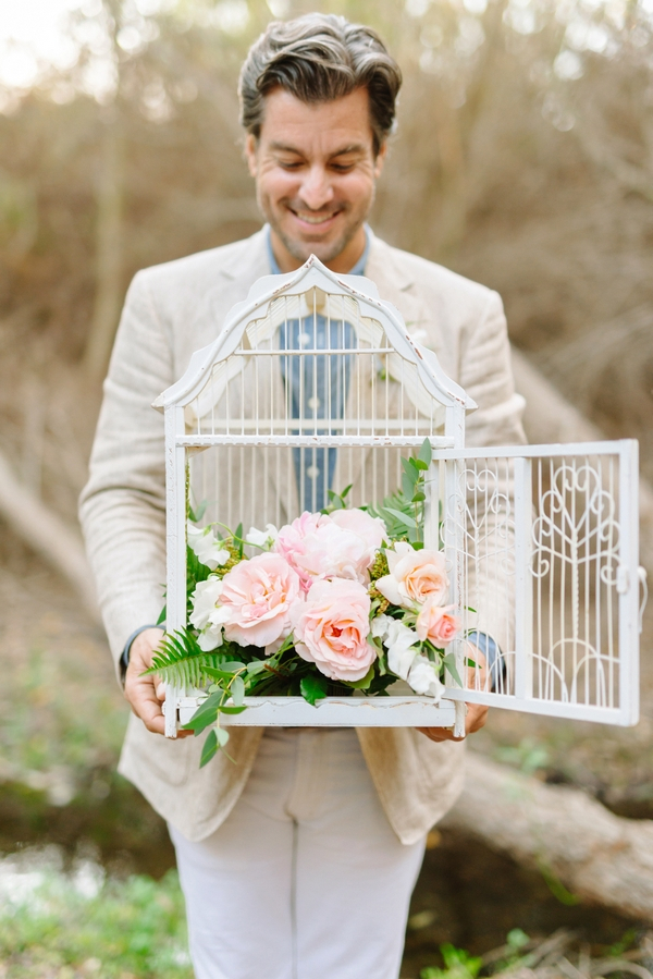 Groom holding birdcage with flowers in