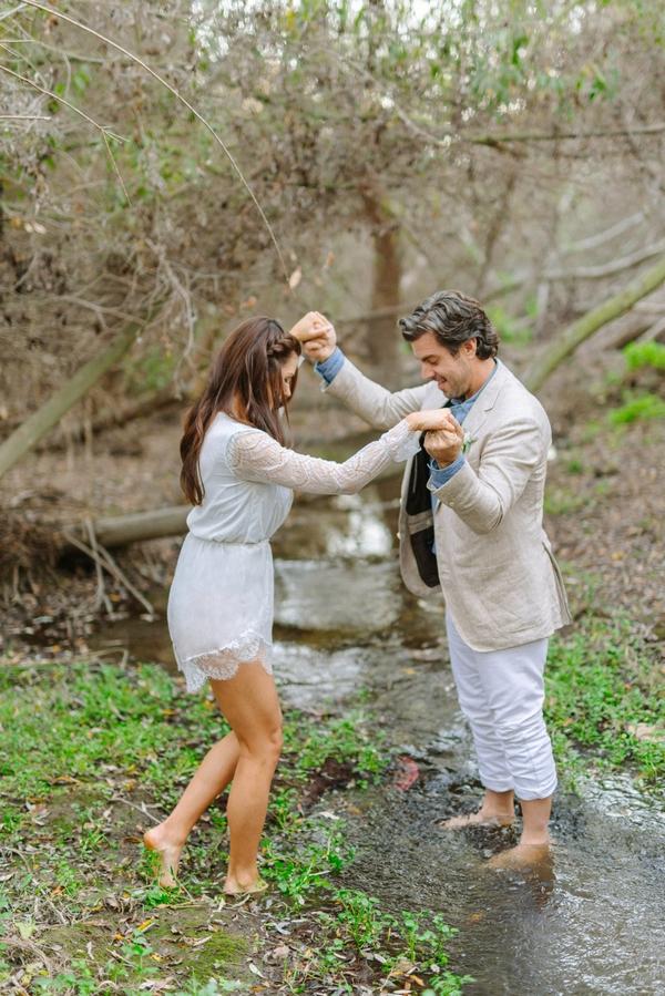 Groom helping bride into creek