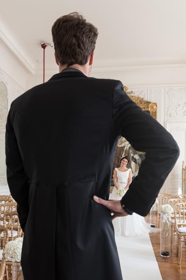Bride seen through groom's arm