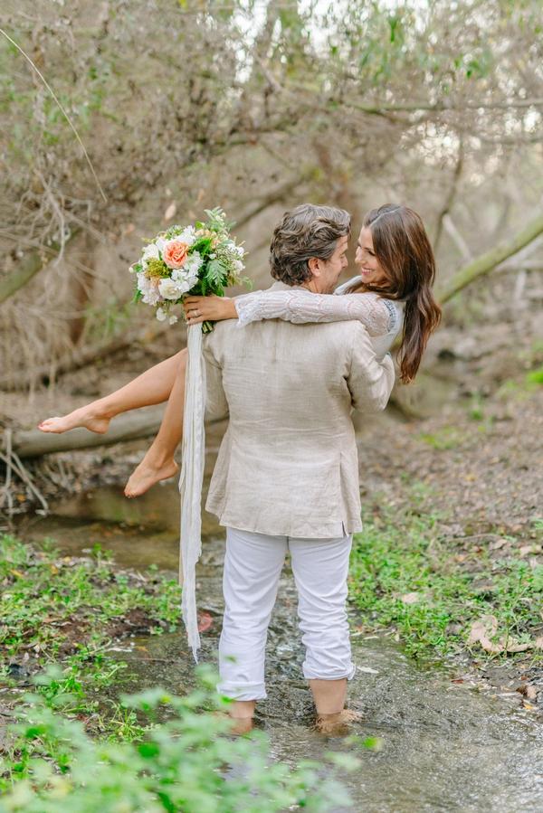 Groom carrying bride in creek