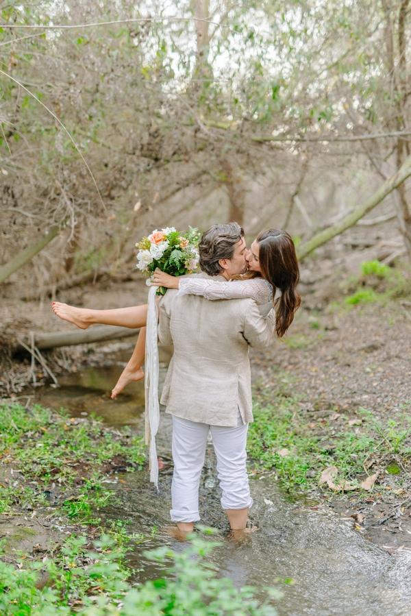 Groom kissing bride in creek