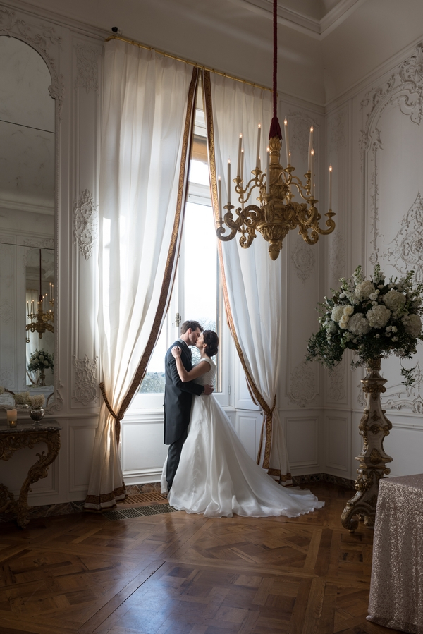 Bride and groom standing by window at Waddesdon Manor