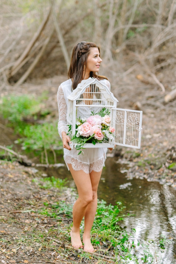 Bride carrying birdcage of flowers