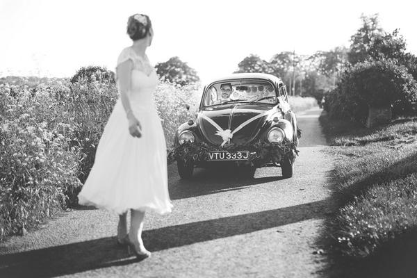 Bride standing in front of VW Beetle