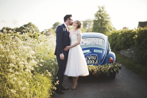 Bride and groom kissing in front of VW Beetle