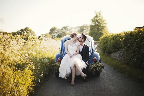 Bride and groom sitting on back of VW Beetle