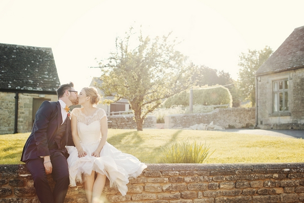 Bride and groom kissing on wall