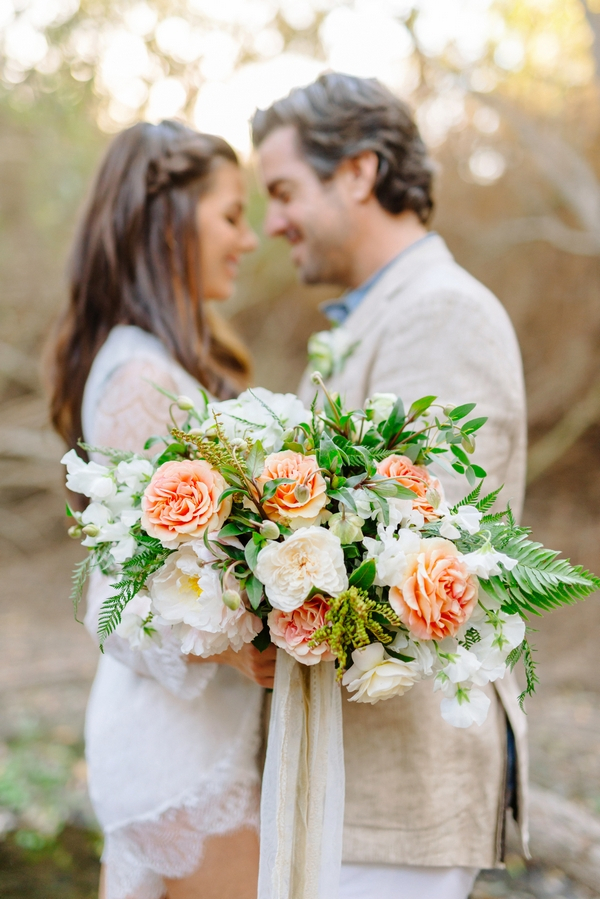 Bride and groom facing each other with large bouquet