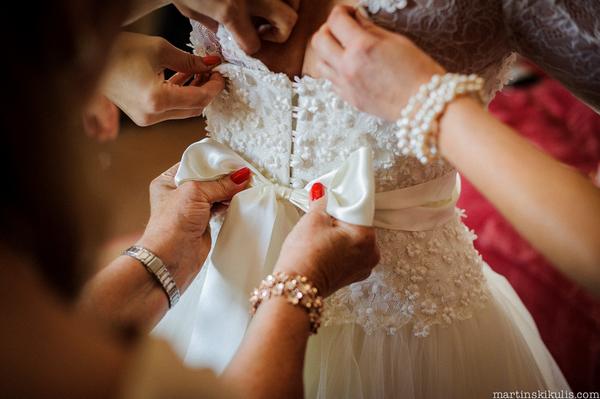 Doing up bow on back of wedding dress