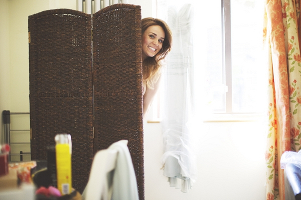 Woman peering out from behind screen