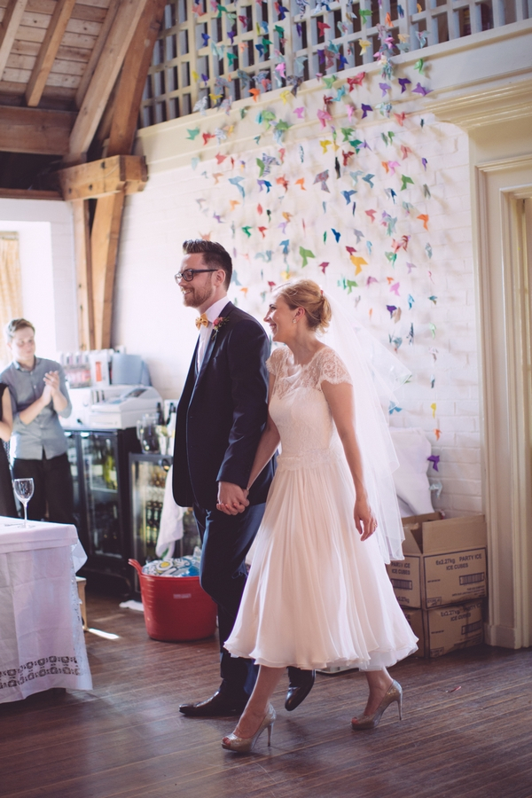 Bride and groom walking in to reception