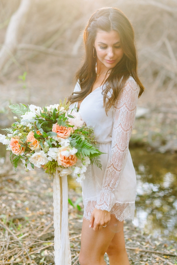 Bride with lace detailed sleeved top holding bouquet