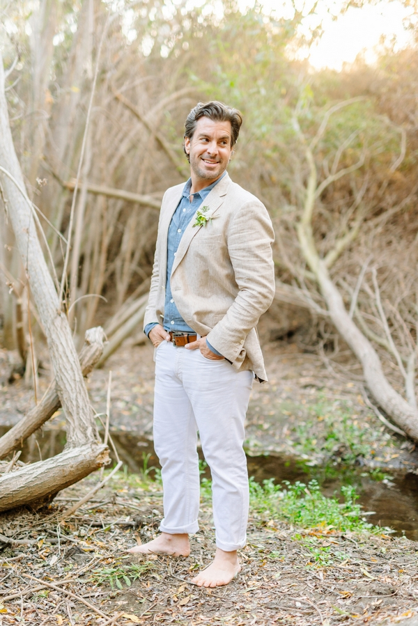 Groom with hands in pockets standing by creek