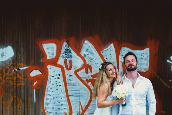 Couple standing in front of graffiti wall in Italy