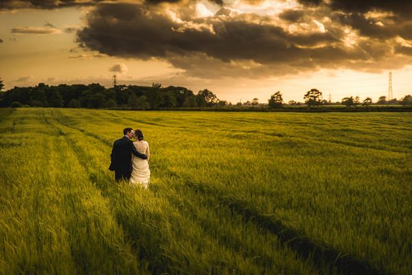 Bride and groom walking through a field - Picture by Andrew Keher Photography