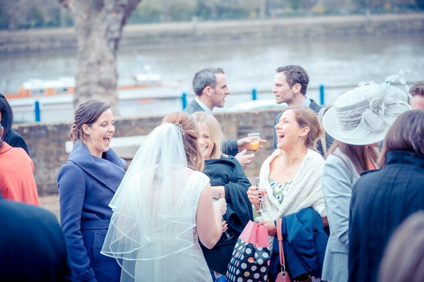 Wedding guests talking to bride by River Thames
