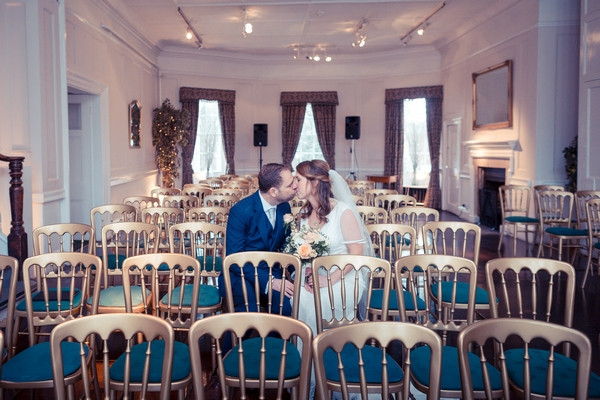 Bride and groom kissing on ceremony chairs