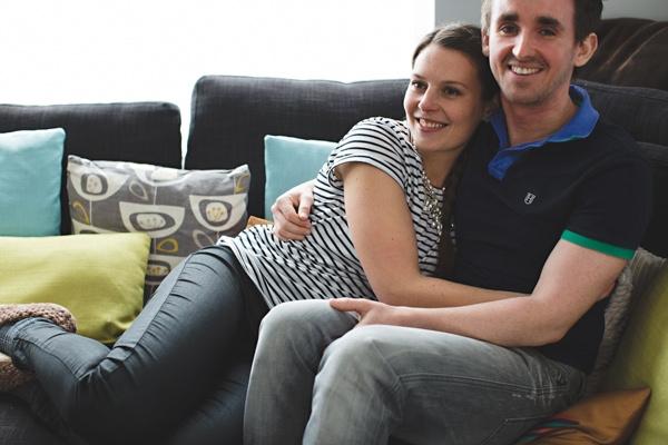 Engaged couple cuddling on sofa