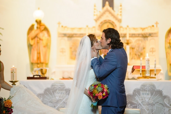 Bride and groom kiss at altar