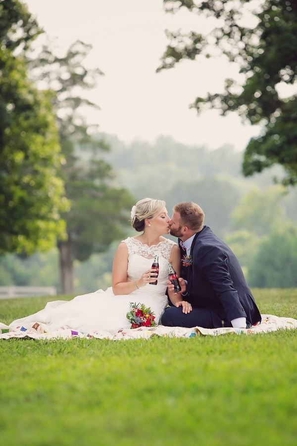 Bride and groom kissing sitting on quilt