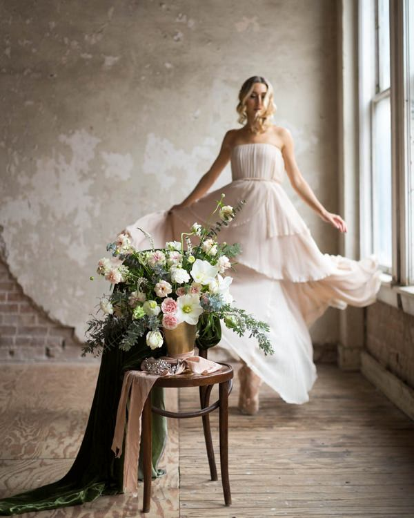 Ballerina bride standing behind chair with bouquet