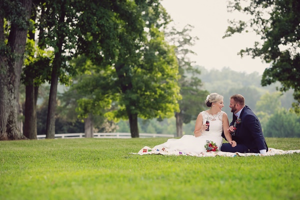 Bride and groom sitting on rug on quilt