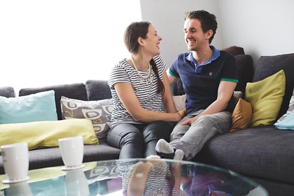 Engaged couple sitting on sofa