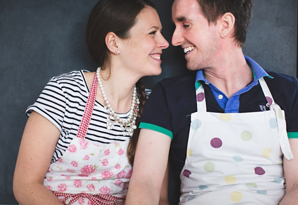 Couple in baking aprons smiling at each other