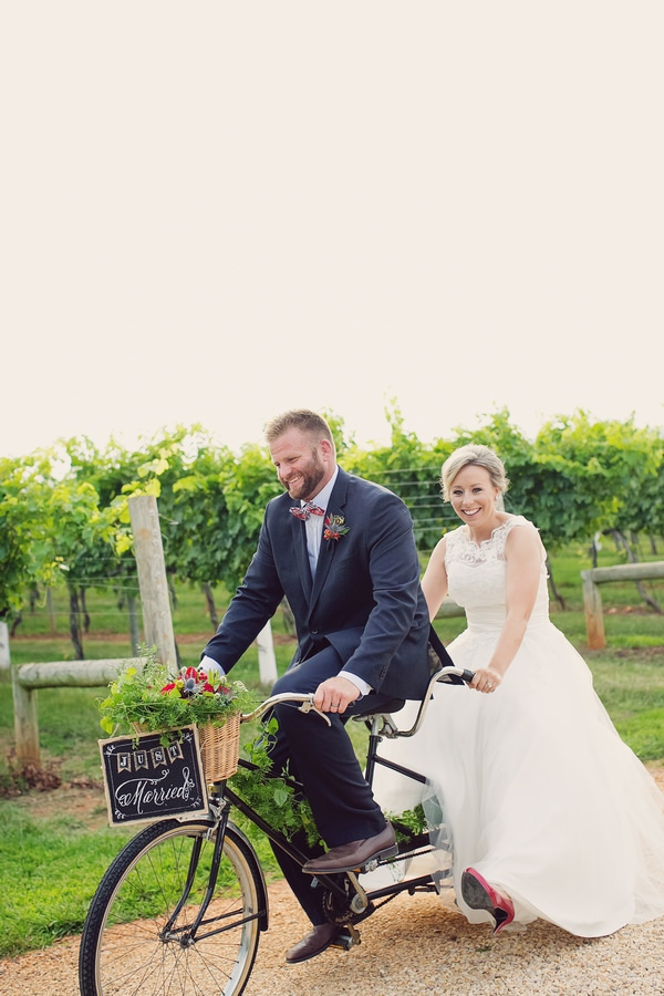 Bride and groom on tandem bicycle cycling past Keswick Vineyards