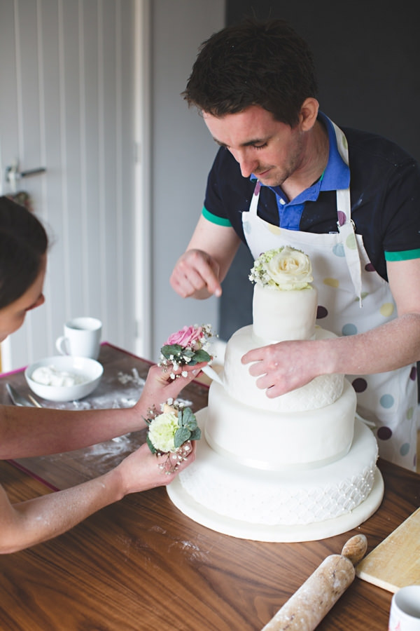 Couple decorating wedding cake