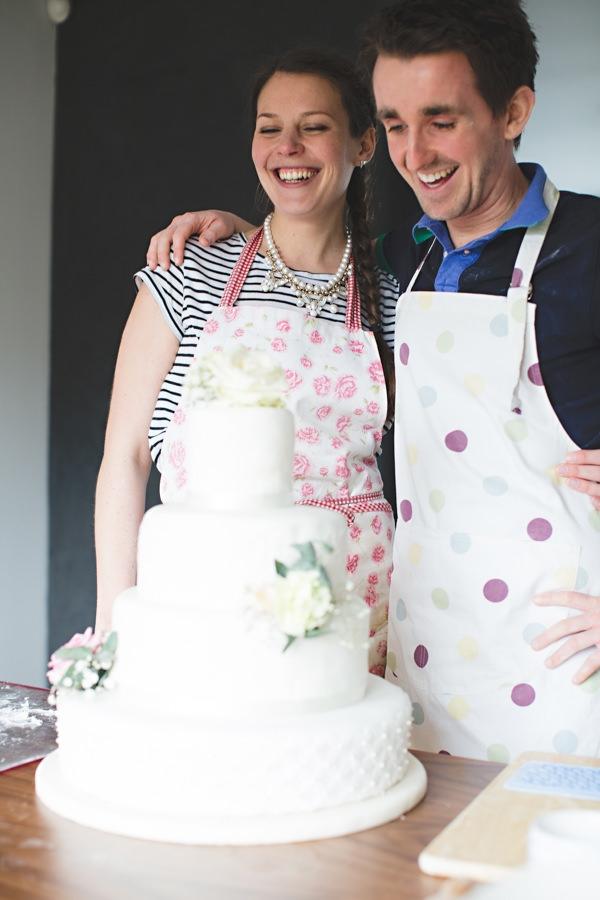 Couple smiling with wedding cake