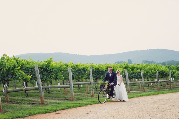 Bride and groom cycling past Keswick Vineyards on tandem